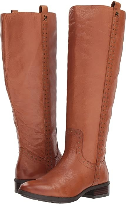 A pair of thigh high boots with rivets along the leg and above the ankle