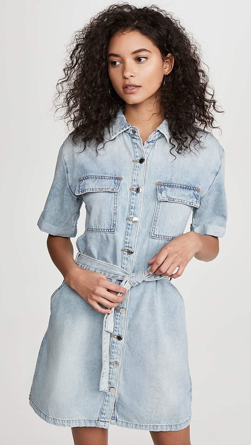 Model wearing the shirtdress with flapped pockets on either side of the chest, silver buttons down the front and a tie around the waist