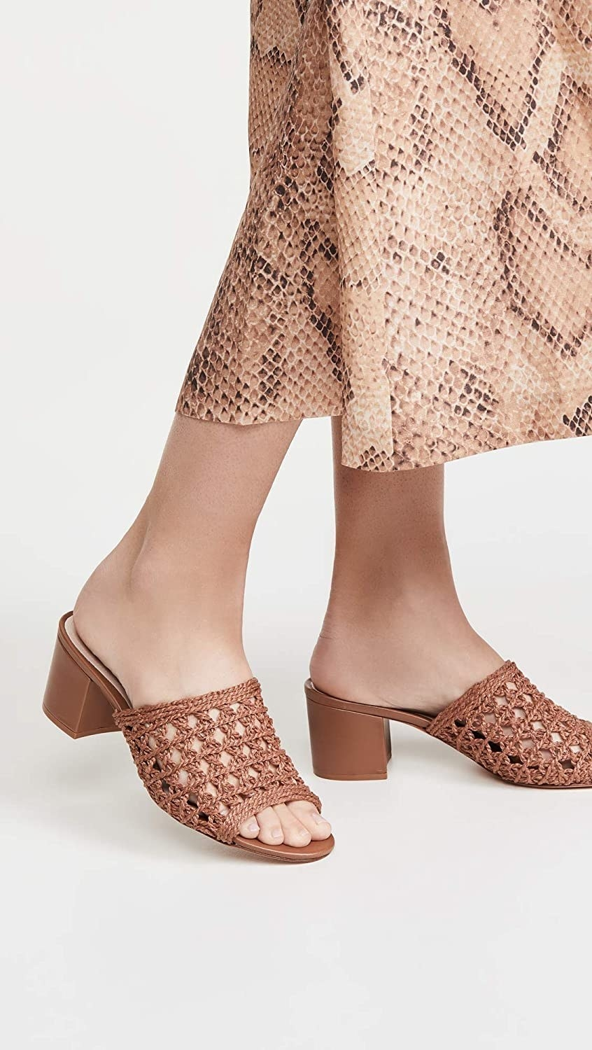 Model wearing the shoes in brown with a block 2.25-inch heel and macrame upper