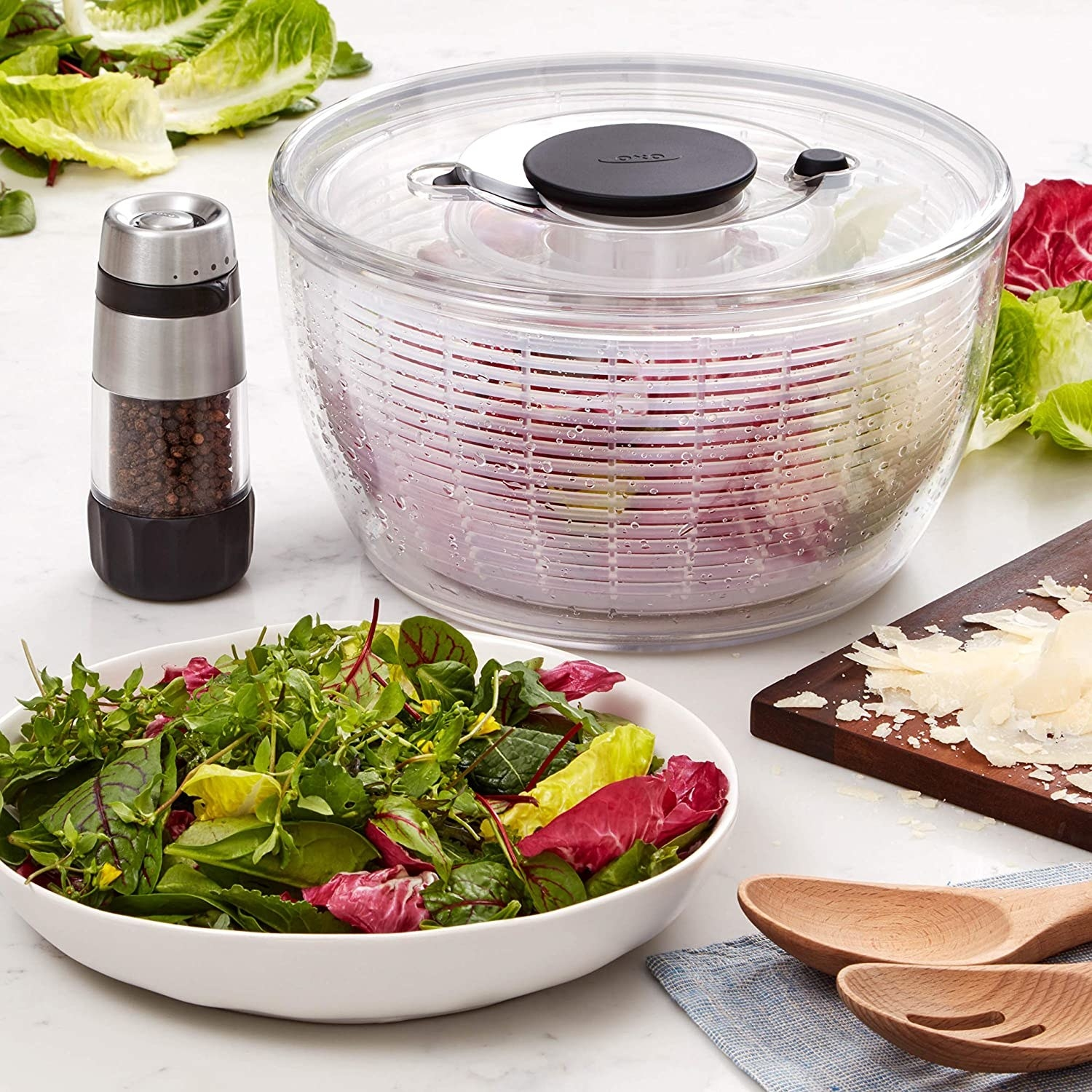 the clear salad spinner next to a bowl of fresh salad