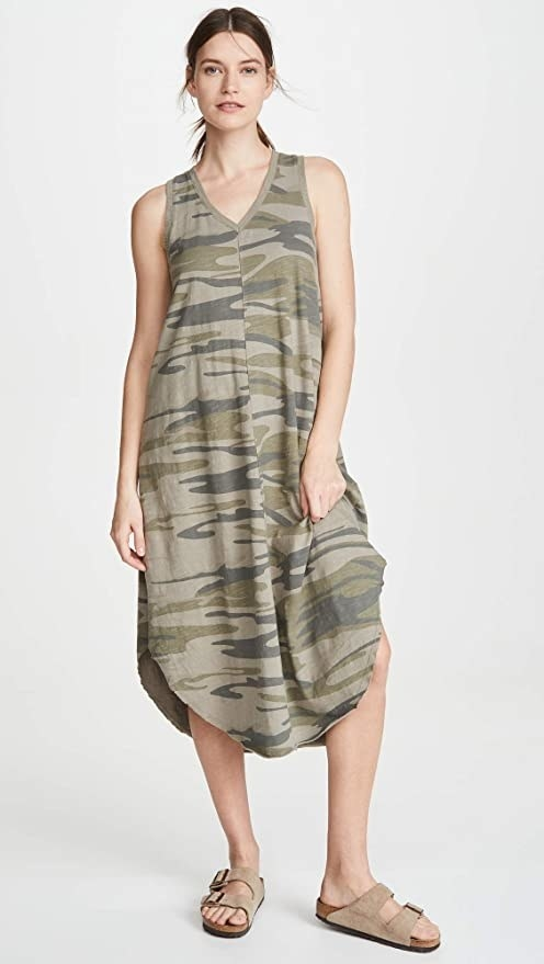 Model wearing the dress in a green camo print with curved hem and v-neck