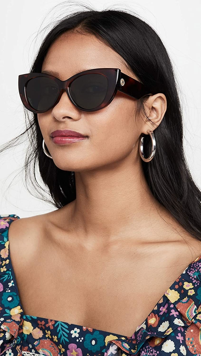 Model wearing the sunglasses with tortoise shell frame and green lense