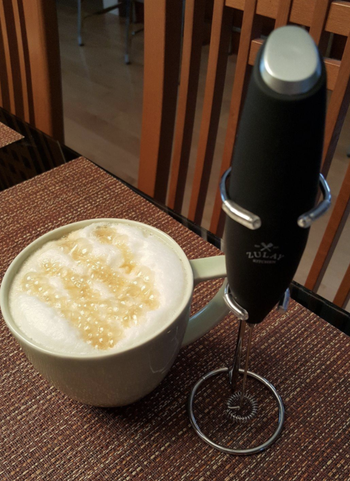 the thin black handheld frother next to a cup of coffee with foamy milk on top