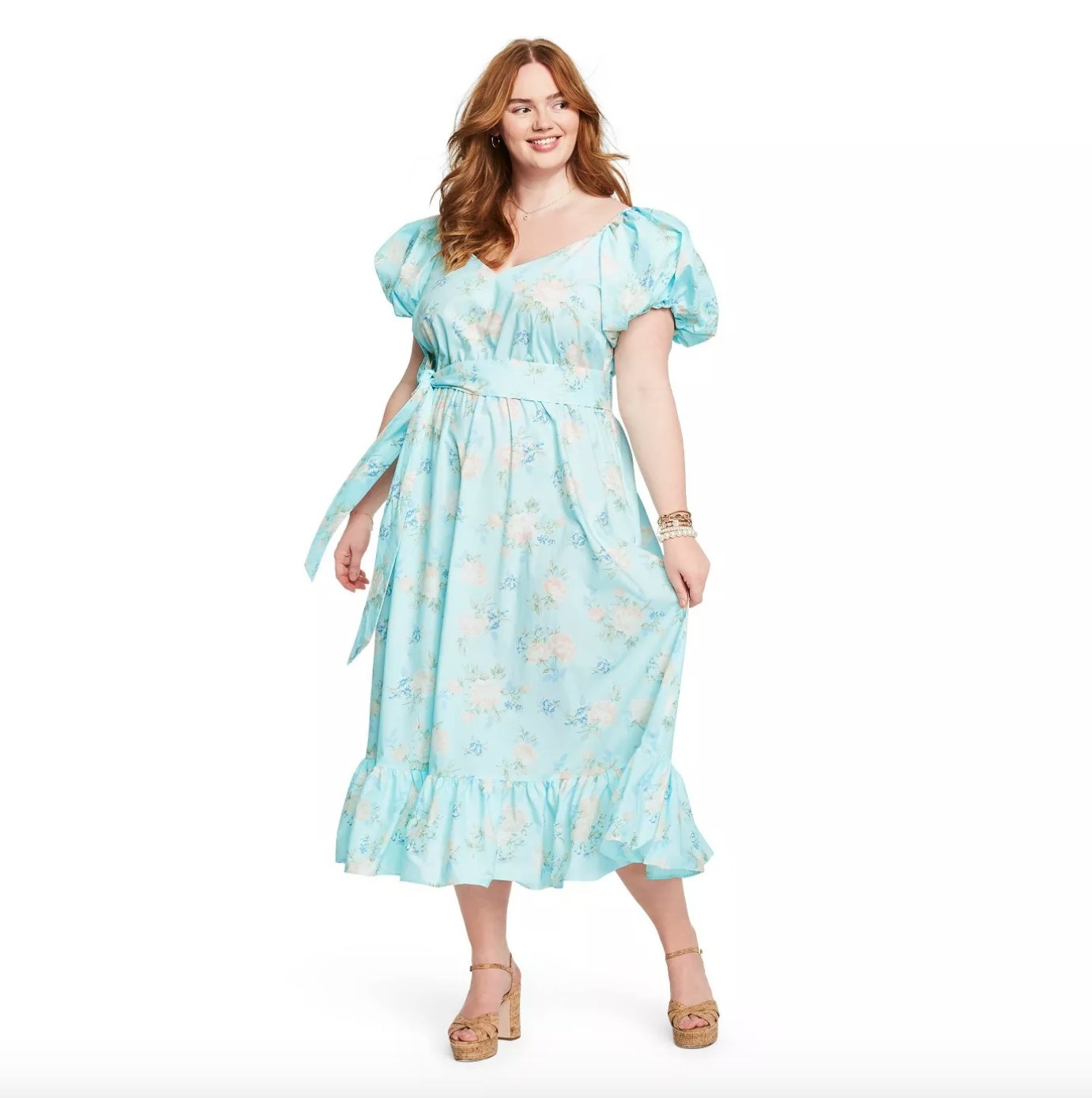 Model wearing the dress in light blue with light pink flowers on it and a ruffle hem