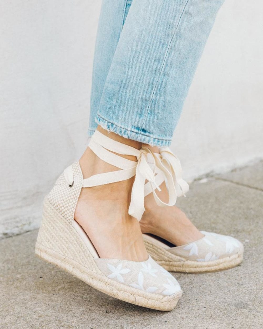 Model wearing the shoes with a 3.50-inch wedge, white floral embroidery on the toe, braided jute around the wedge, and a beige tie around the ankle