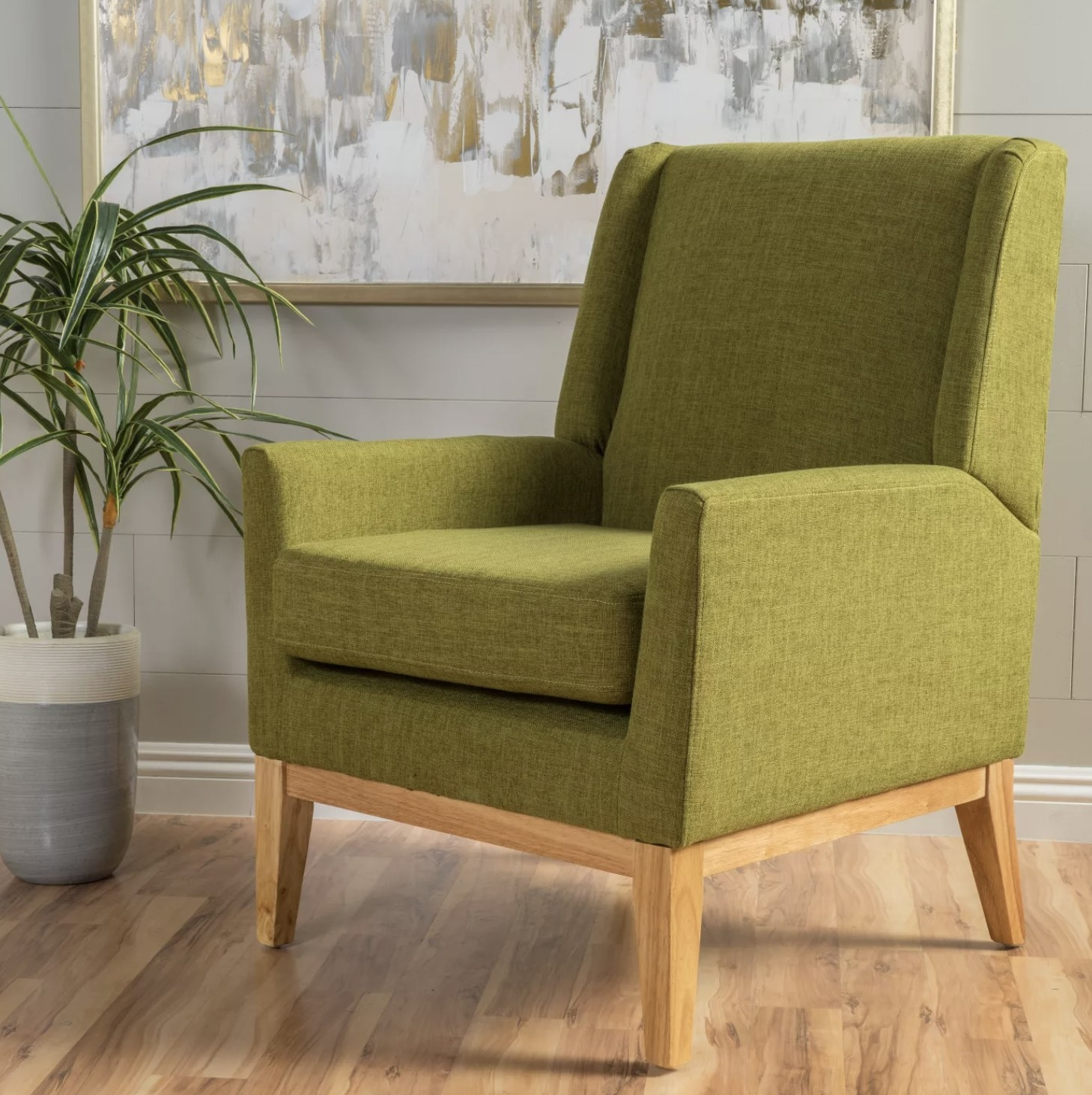 A green upholstered chair with light wood legs