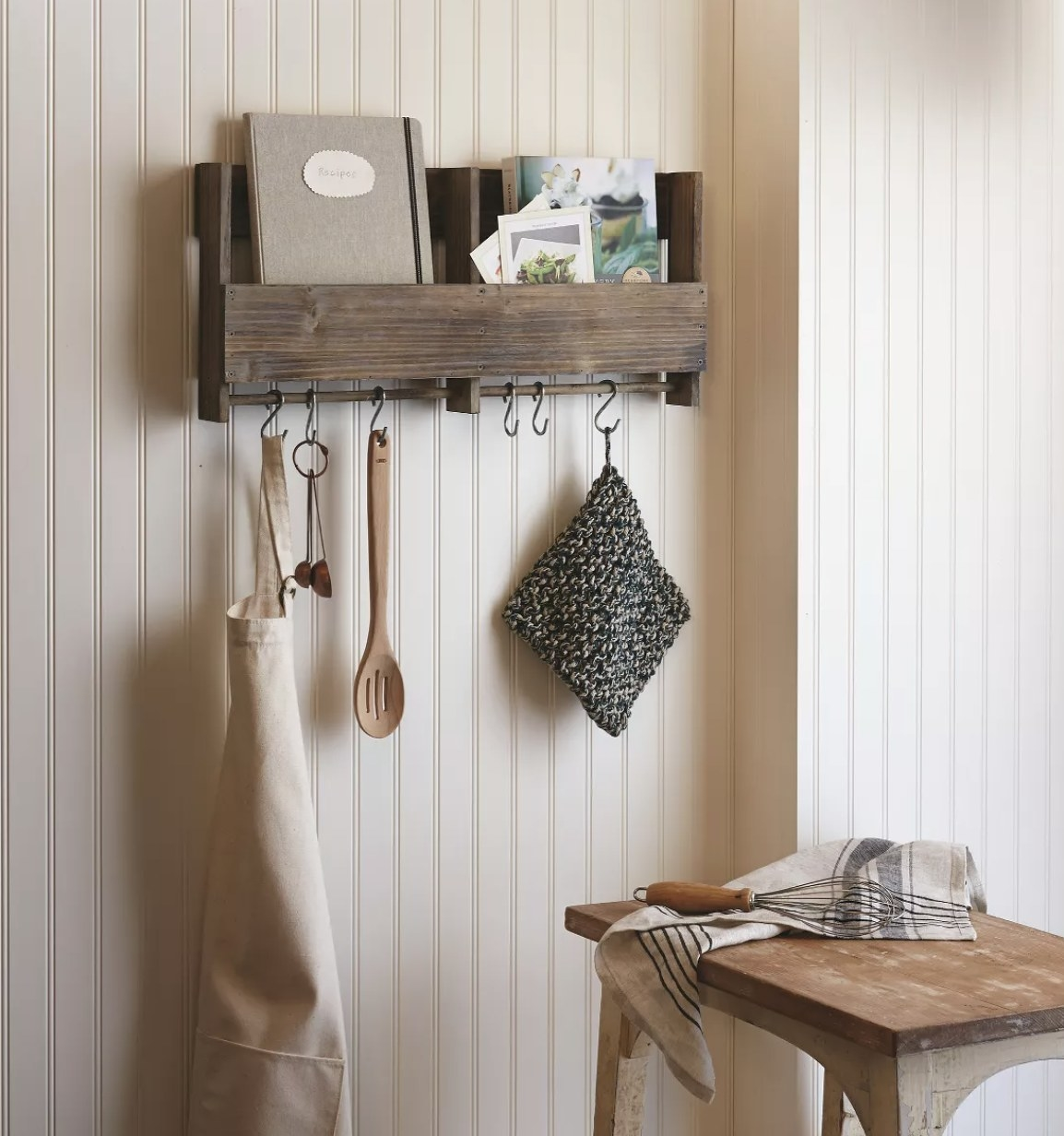 A wooden shelf attached to a wall with a bar to hang things from