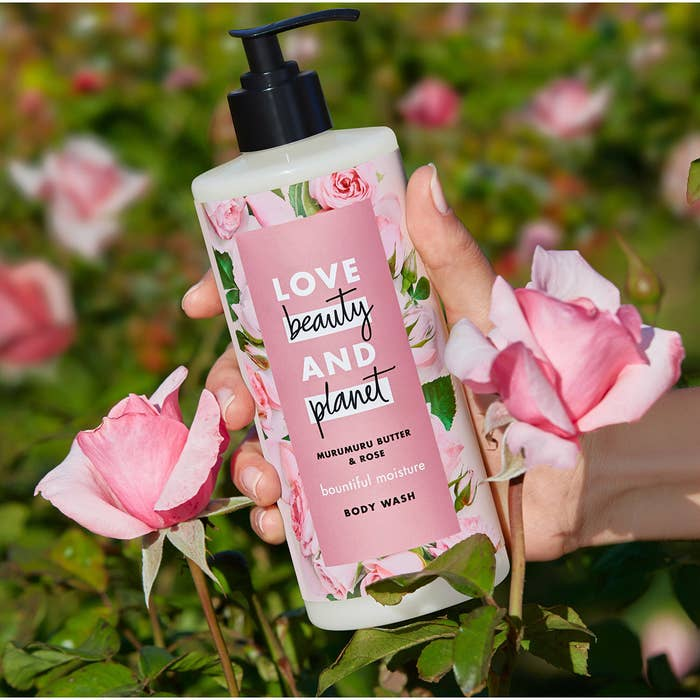 a handle holding the pump bottle of murumuru butter and rose body wash, the bottle is covered in pink roses