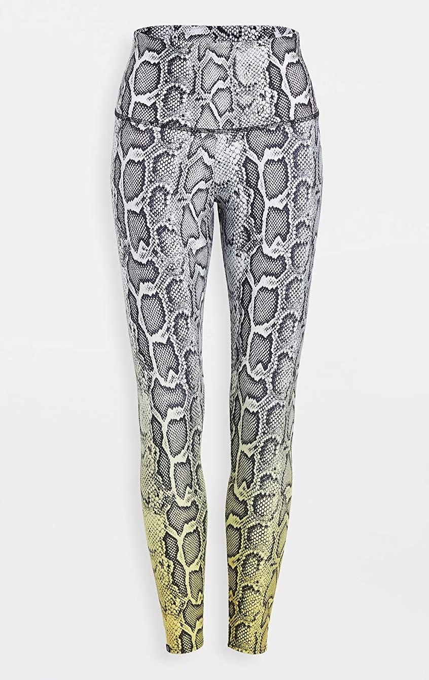The leggings with black and white snake print at the top with a high waistband and coloring that goes to yellow down by the ankles