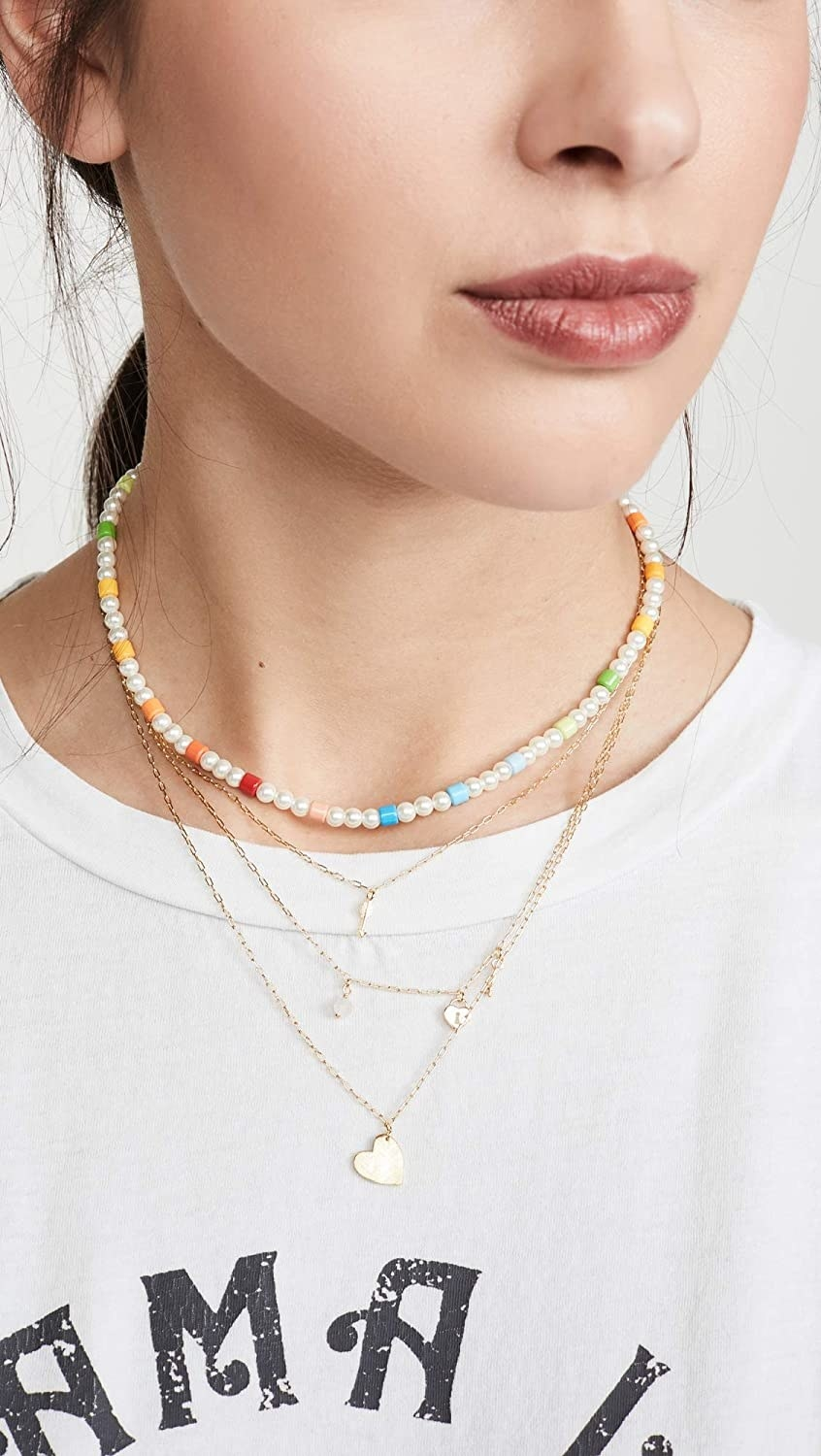 Model wearing the gold tone necklace with heart and other charms