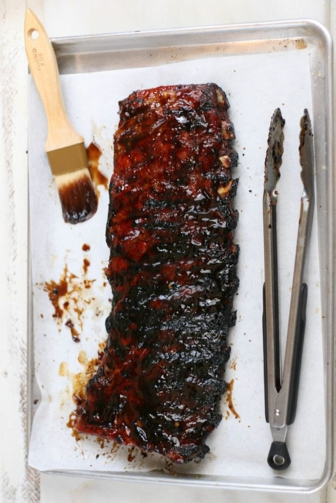 A rack of sticky glazed ribs on a baking sheet with a brush and tongs to the side.
