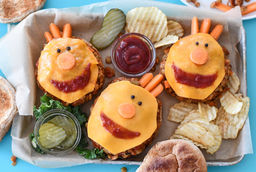 Sloppy Joes with their top bun off and smiley faces made with cheese and ketchup.