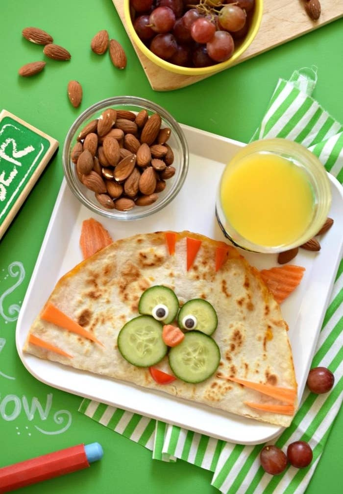 Quesadilla with a cat's face made from cucumbers, carrots, and peppers.