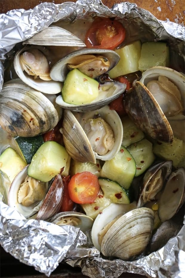 Grilled littleneck clams in a foil packet cooked with tomatoes, zucchini, and red pepper flakes.