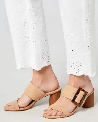 Model wears beige block heel sandals with white pants