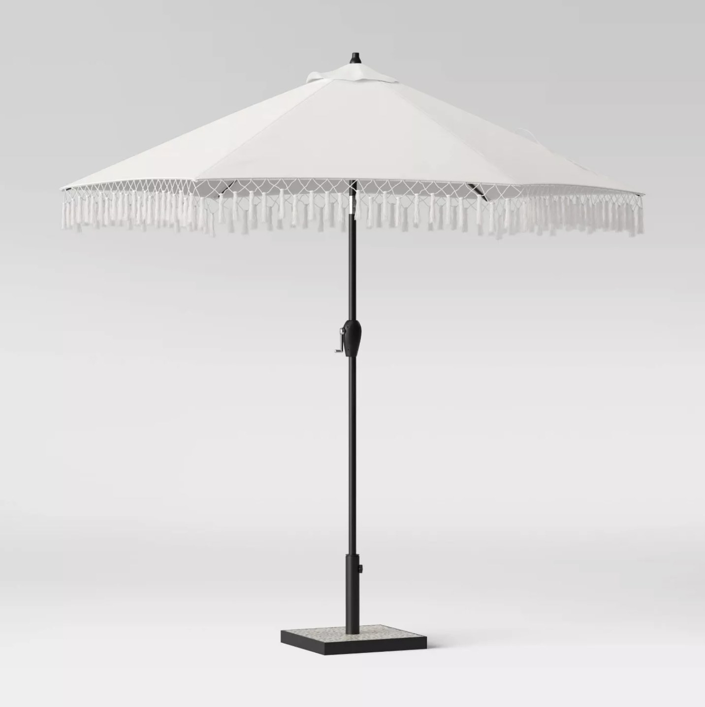 A white patio umbrella with tassels on the edges on a black stand