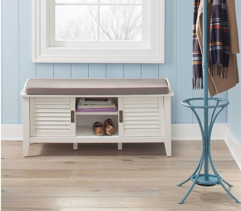 the white storage bench with a gray cushion