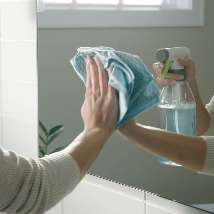 A models hand wiping down a bathroom mirror while using the spray bottle