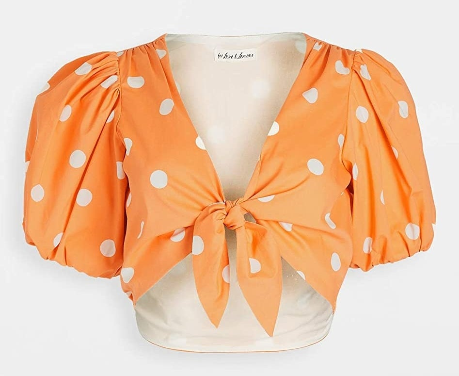 The orange top with white polka dots and short puff sleeves