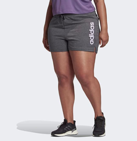 "Model wears grey adidas running shorts that say ""adidas"" in purple lettering"