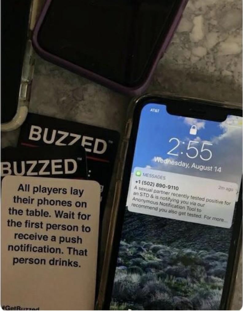 A game card saying to show your phone to the other players and a phone with a text notification about an STD
