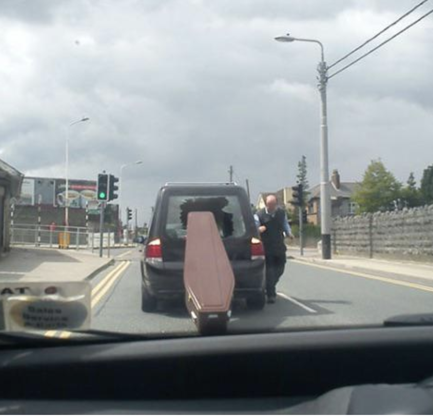 A coffin has smashed through the back window of a hearse