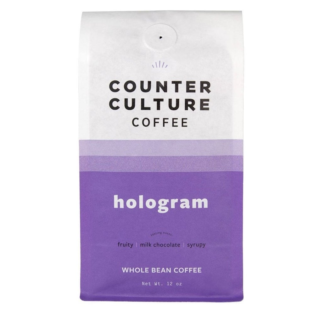 A purple and white bag of coffee beans
