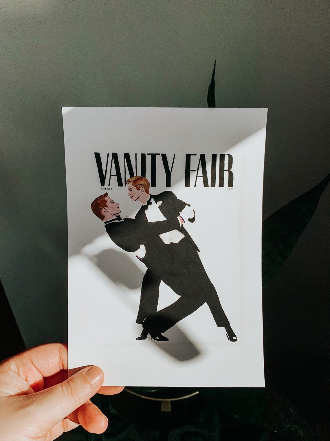 """Two people in traditional black tie suits dancing romantically together with """"Vanity Fair"""" written above them"""