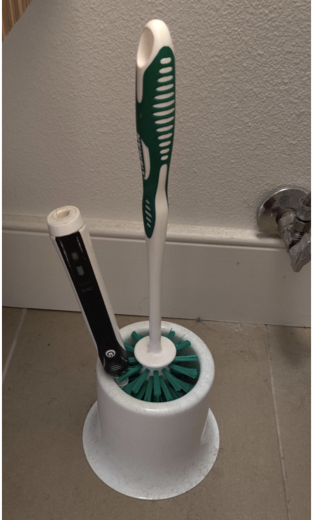 A phone stuck in the toilet brush holder