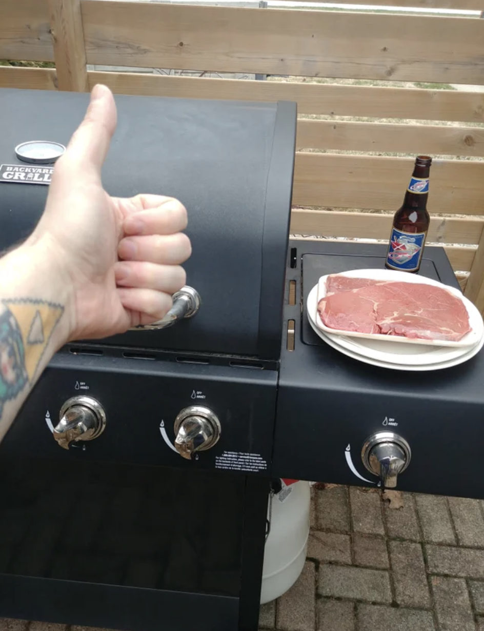 A man gives a thumbs up while cooking a steak and drinking a beer alone