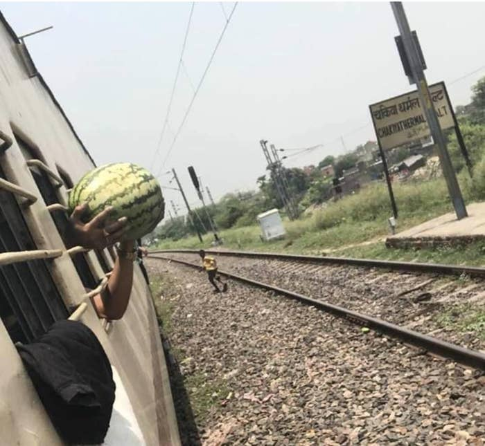 A man holds a watermelon outside the windows of a moving train