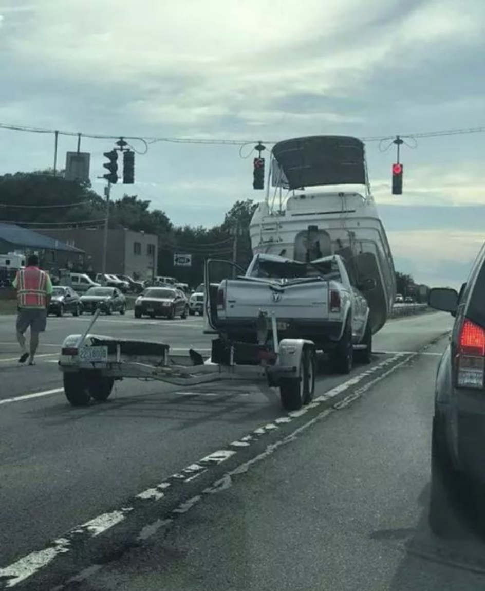At a stop light a boat has gone over the top of a truck, denting it