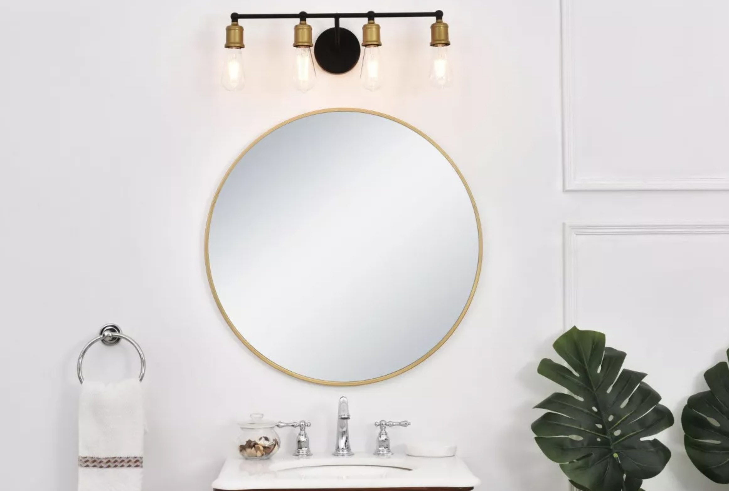 A vanity light with four naked bulbs above a bathroom sink