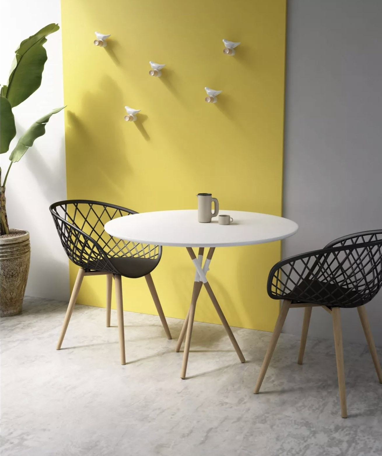 A white round dining table with three intersecting light wood legs