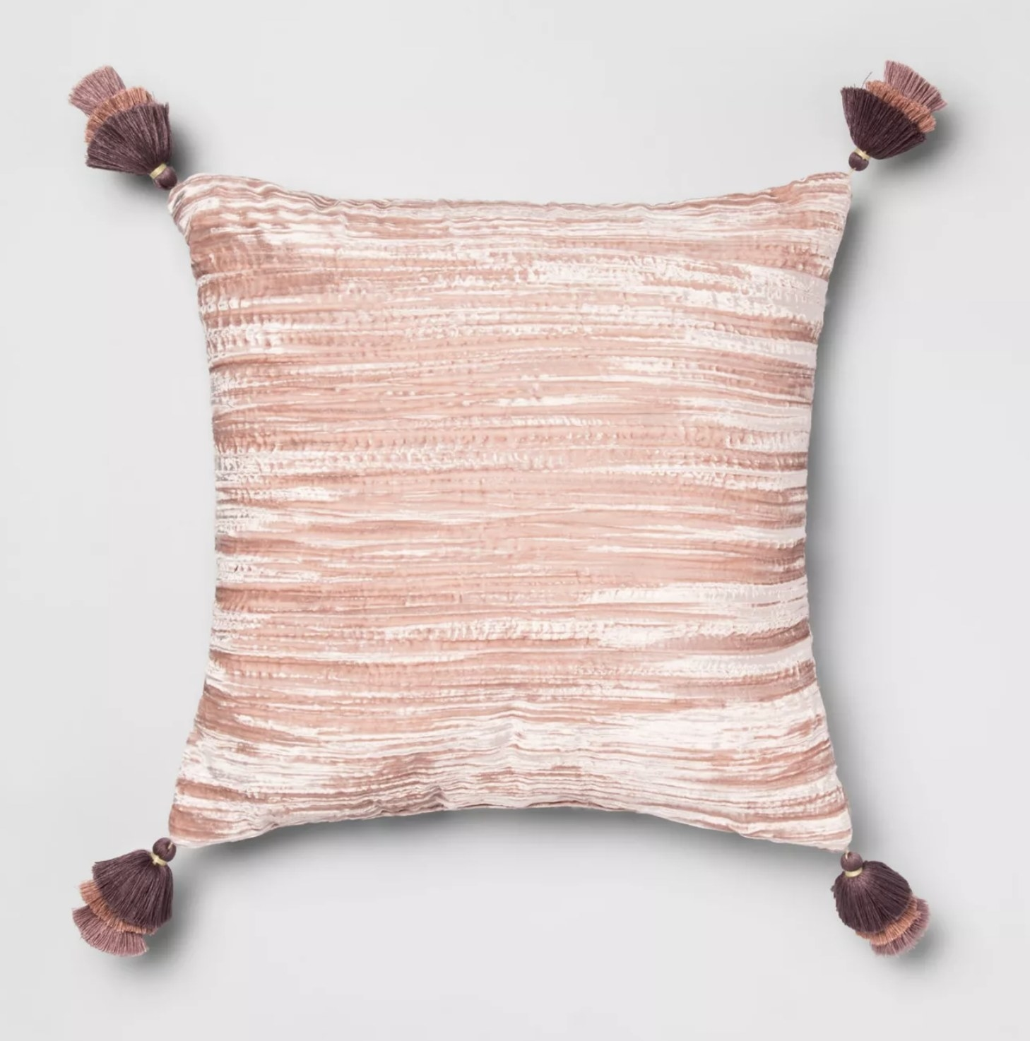 A pink velvet throw pillow with purple tassels