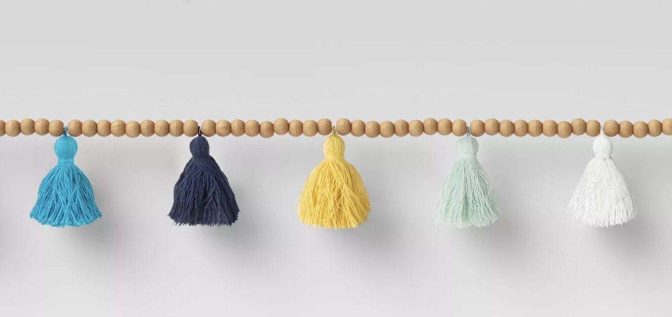 A wooden bead garland with multicolored tassels