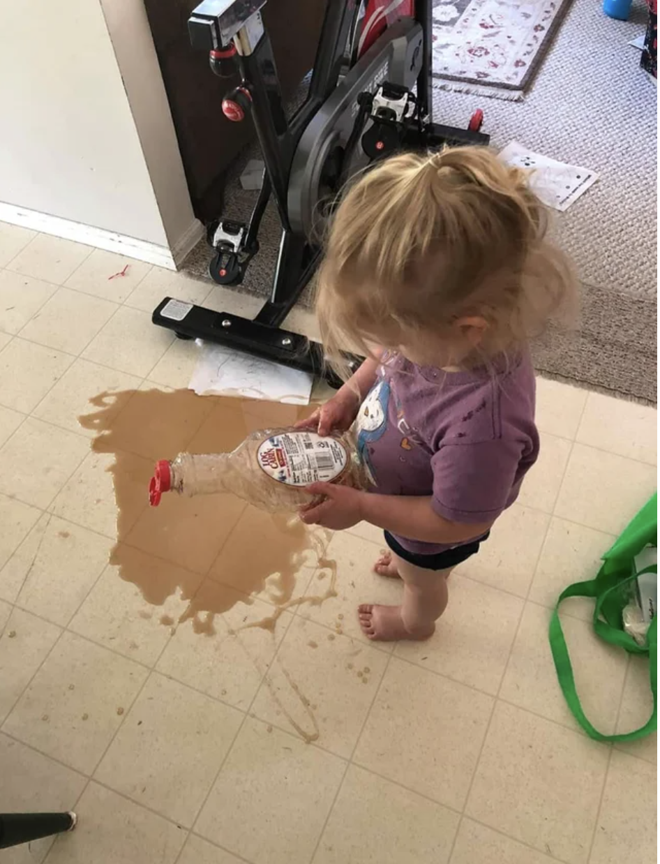 A child holding an empty syrup bottle and looking at syrup on the floor