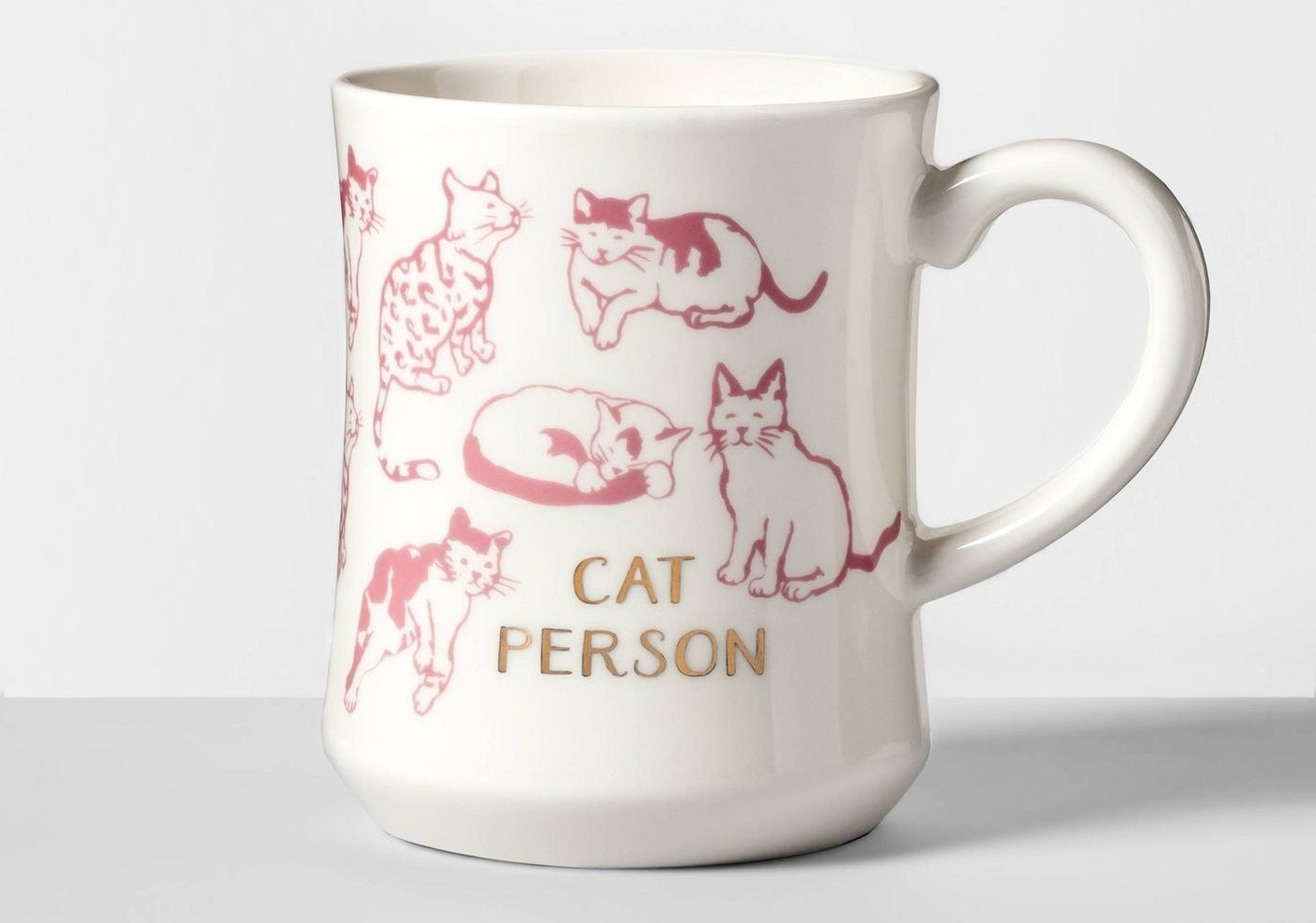 "A white ceramic mug with pink cats that says ""Cat Person"""