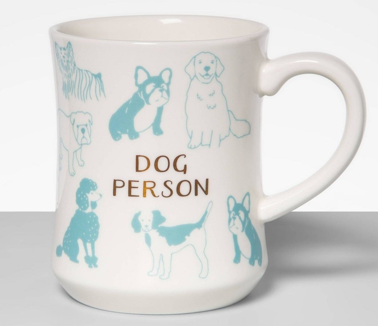 "A white ceramic mug with teal dogs that says ""Dog Person"""