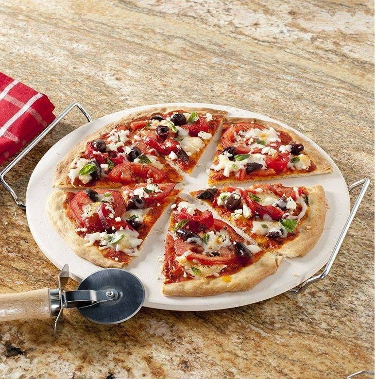 A pizza on a place next to a pizza cutter wheel