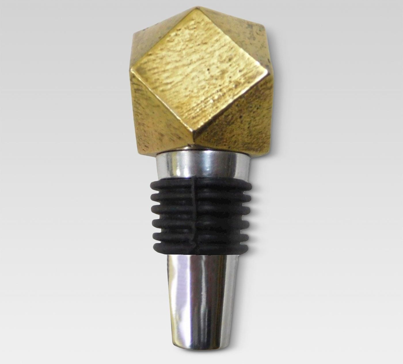 A metal bottle stopper with black rubber and a golden geometric top