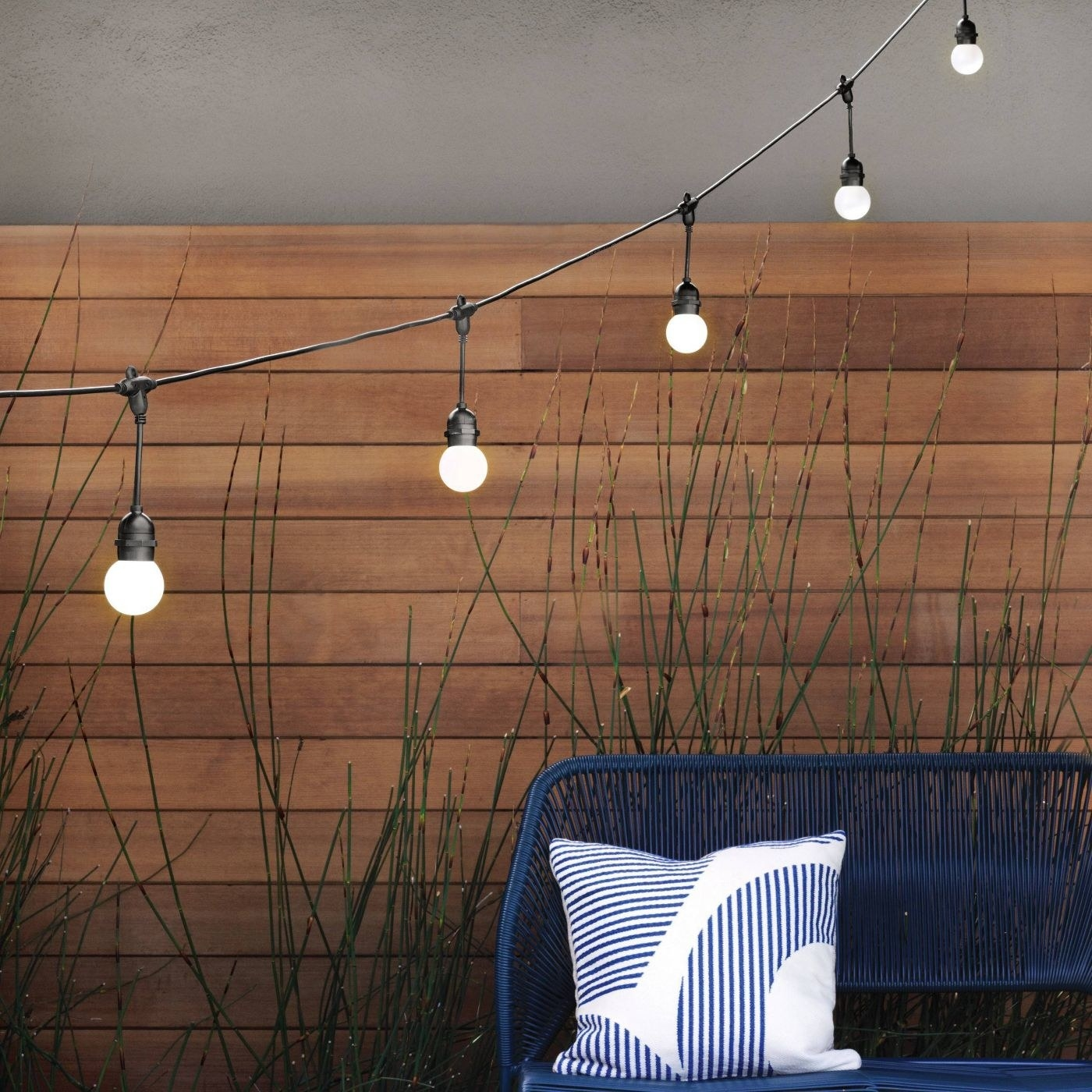 A string of round light bulbs hanging outdoors
