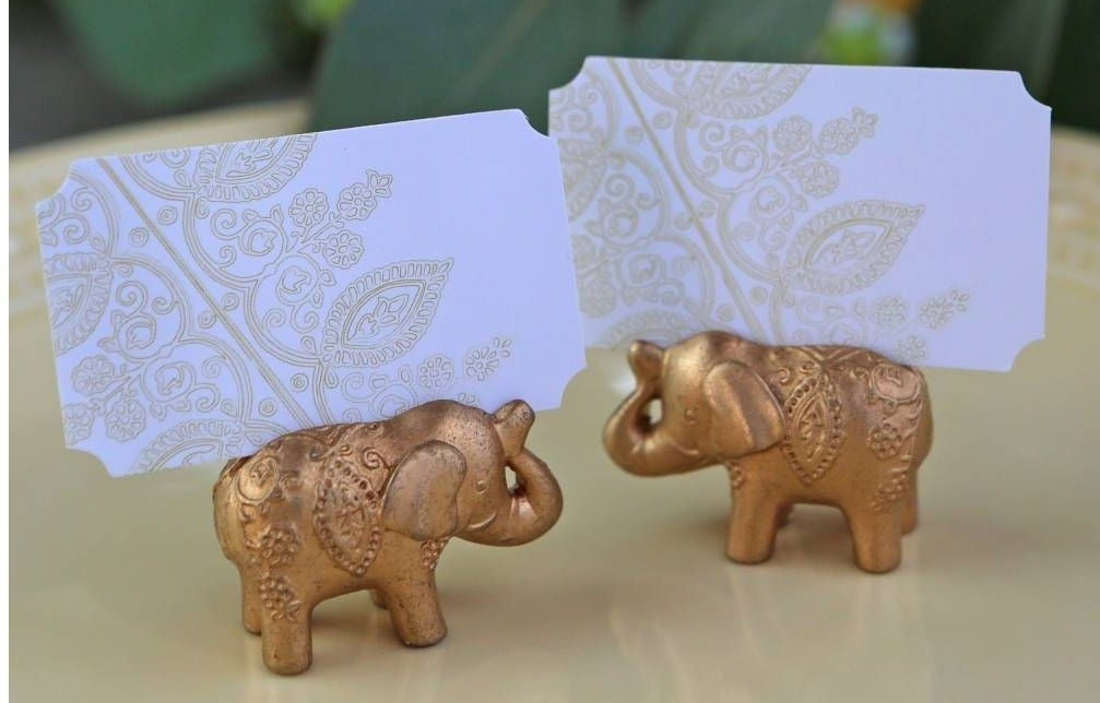 Two ornate golden elephants holding place cards
