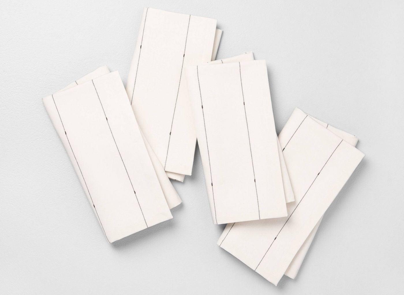 Four white cloth napkins with stripes