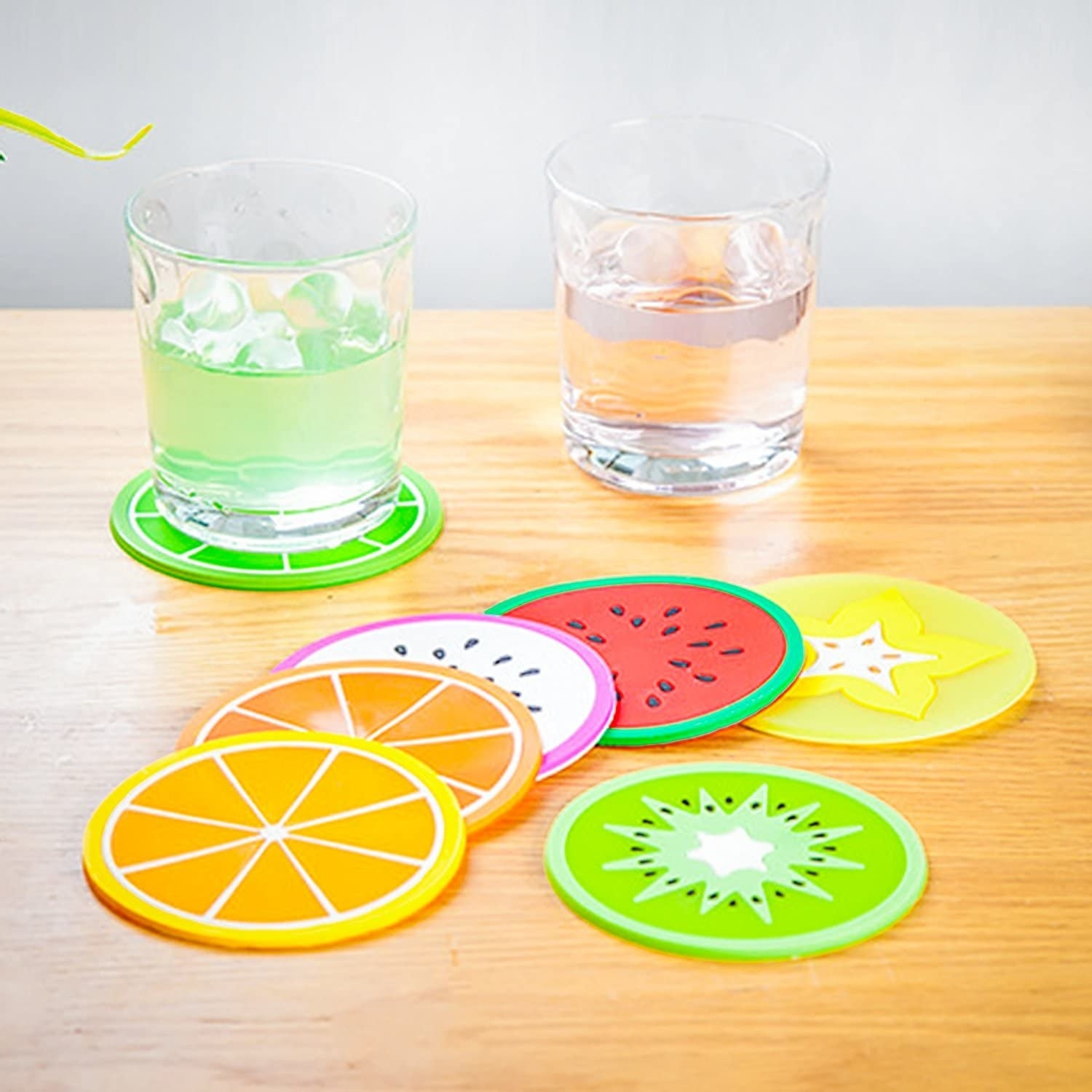 A set of round silicone coasters on a table They each look like a different sliced fruit