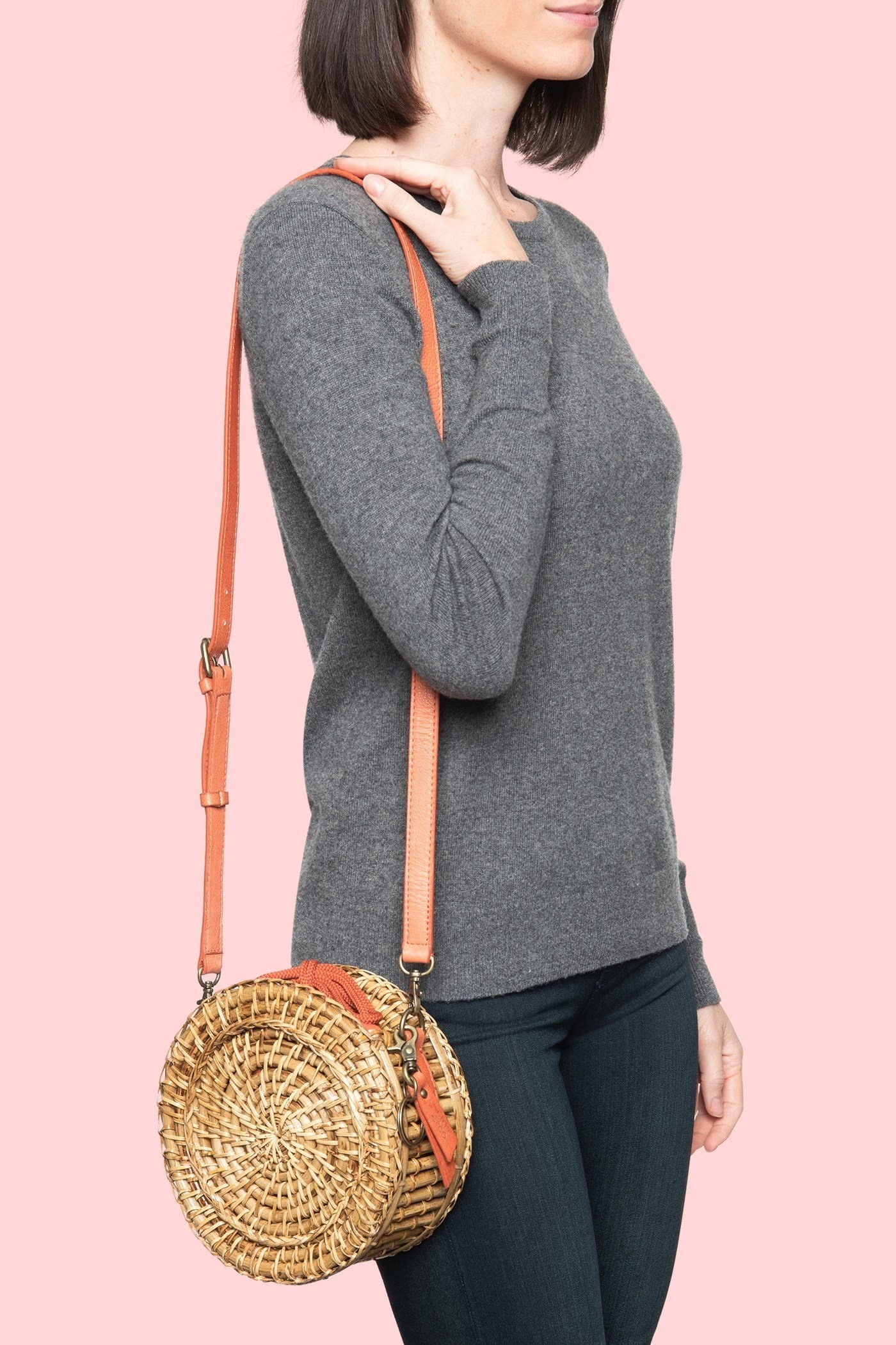 Model wearing the straw circular bag with orange tie and strap over their shoulder