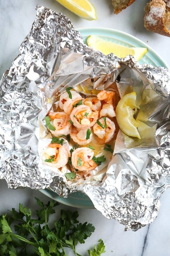Shrimp in scampi sauce with fresh parsley and lemon wedges in a foil packet.