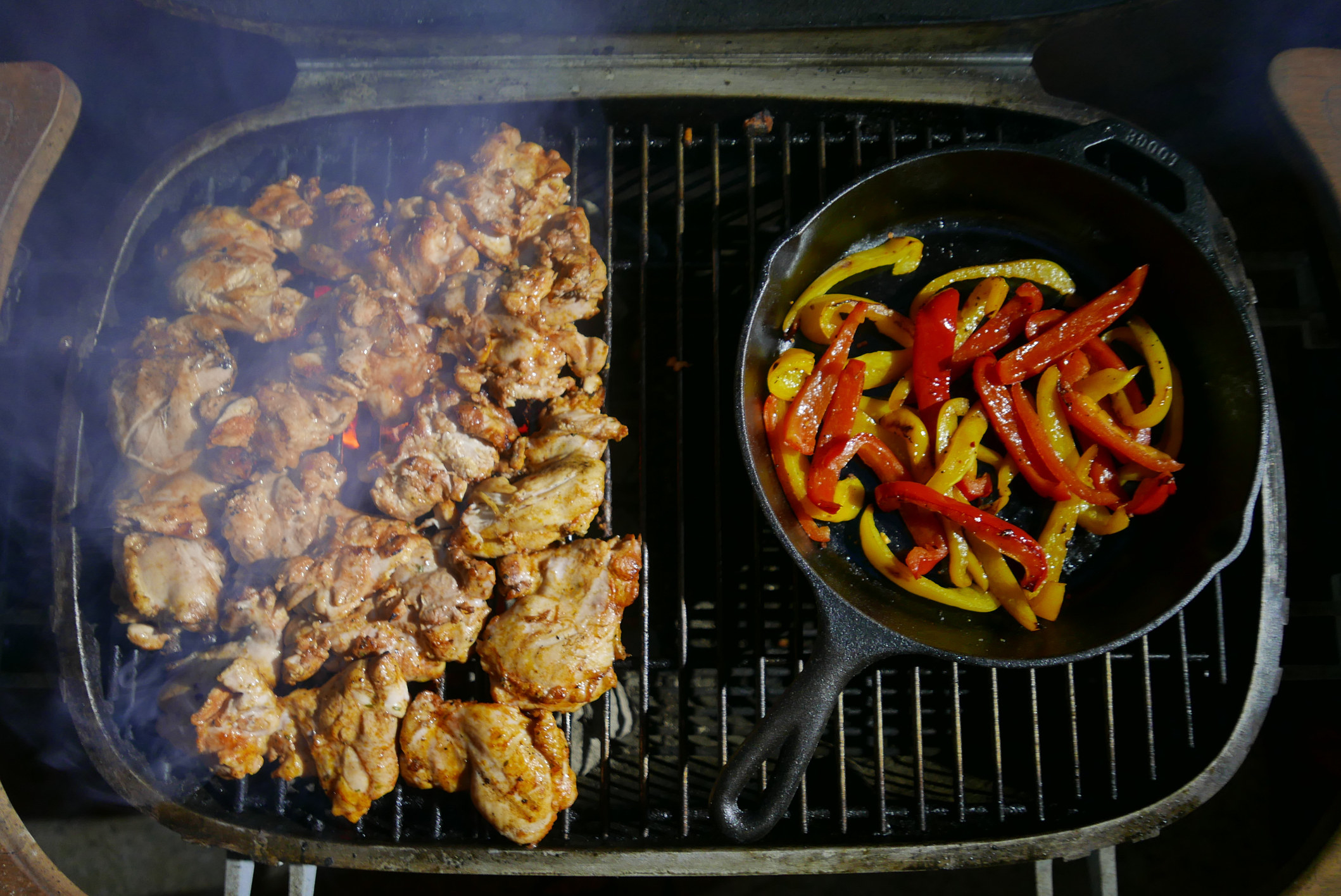 Chicken a cast iron skillet filled with bell peppers going on a grill.