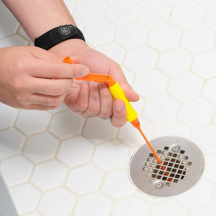 Hands twisting the handle with the snake down the grate of a flat drain
