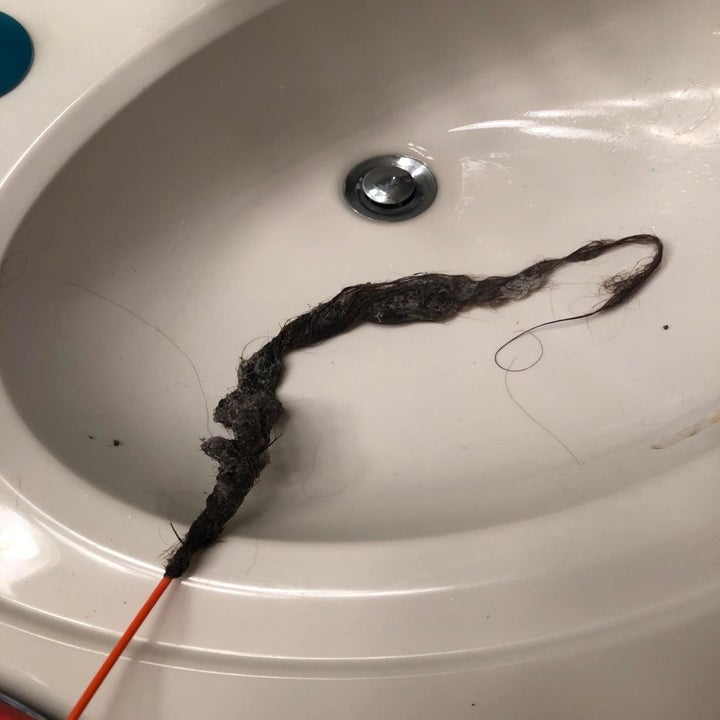 A reviewer's long hair clog pulled out of a sink drain